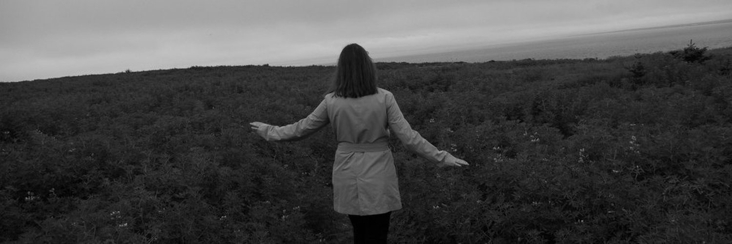 A person wearing a jacket walking through a field of lupine with the ocean in the background